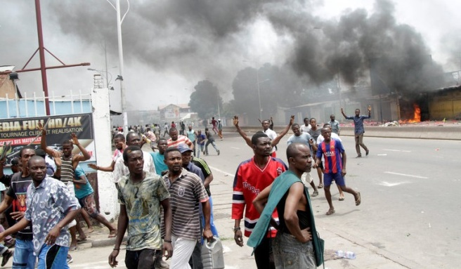 21 September 2016. Kinshasa, Democratic Republic of Congo — Busted glass. Smoldering fires. Torched cars. Empty streets. Hundreds of police officers clumped on the corners, glancing up at the smoke uncurling in the sky. Photo: New York Times